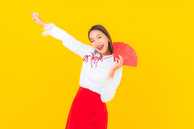 Portrait beautiful young asian woman with red envelopes letter in chinese new year on yellow