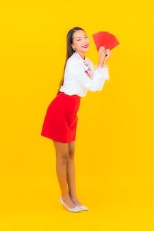 Портрет красивой молодой азиатской женщины с красным конвертом в китайском новом году на желтом Бесплатные Фотографии