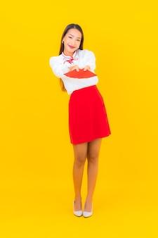 黄色の旧正月に赤い封筒の手紙を持つ美しい若いアジア女性の肖像画