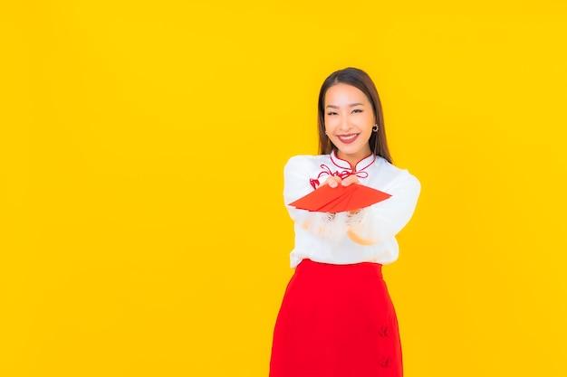 黄色の旧正月に赤い封筒の手紙を持つ美しい若いアジア女性の肖像画 無料写真