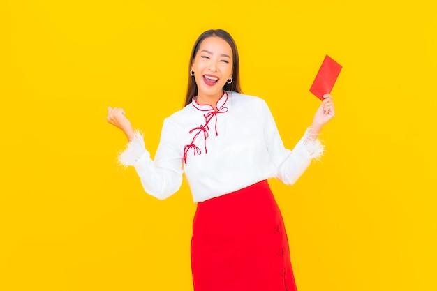 노란색에 중국 새 해에 빨간 봉투 편지와 초상화 아름 다운 젊은 아시아 여자