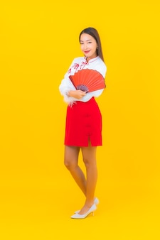 Portrait beautiful young asian woman with red envelopes letter on yellow
