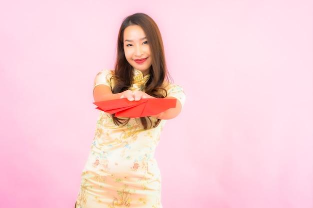 Женщина портрета красивая молодая азиатская с красными конвертами на розовой стене