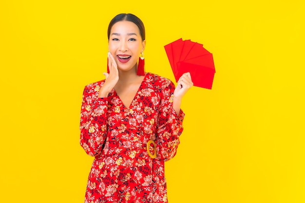 Portrait beautiful young asian woman with red envelopes on yellow wall