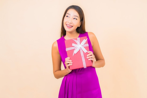 Portrait beautiful young asian woman with red gift box on color isolated background