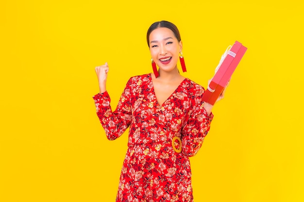 Portrait beautiful young asian woman with red gift box on color wall