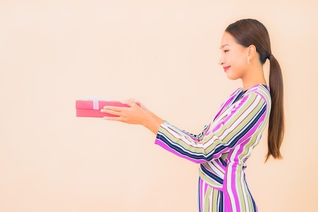Bella giovane donna asiatica del ritratto con il contenitore di regalo rosso sul colore