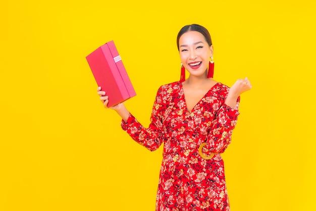 色の壁に赤いギフトボックスと肖像画美しい若いアジアの女性