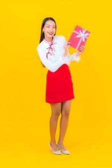 黄色に赤いギフト ボックスを持つ美しい若いアジアの女性の肖像画