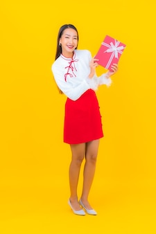 Portrait beautiful young asian woman with red gift box on yellow