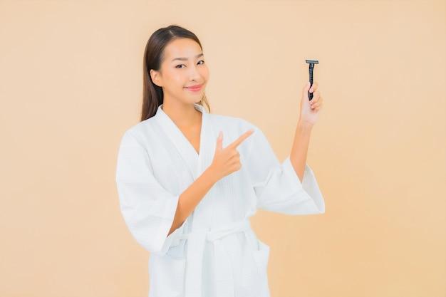 Bella giovane donna asiatica del ritratto con la rasatura sul beige