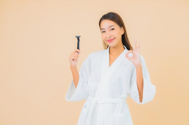 ベージュのシェービングを持つ肖像画美しい若いアジアの女性