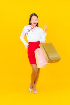 Женщина портрета красивая молодая азиатская с хозяйственной сумкой и кредитной картой на желтом