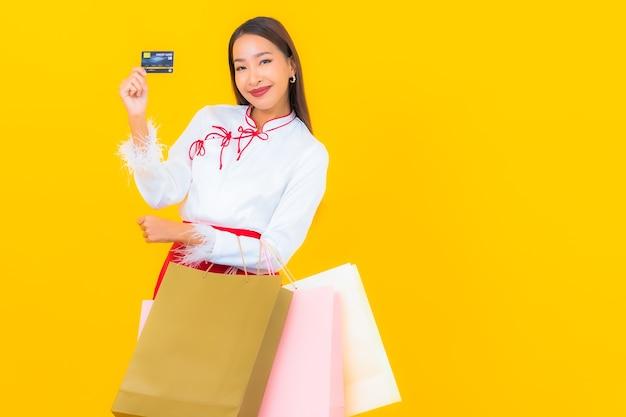 黄色のショッピング バッグとクレジット カードを持つ美しい若いアジア女性の肖像画