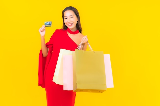 ショッピングバッグとクレジットカードを持つ肖像画の美しい若いアジアの女性