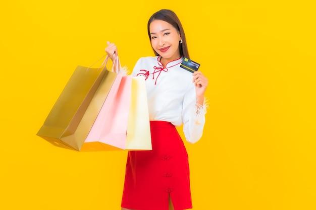 Ritratto bella giovane donna asiatica con borsa della spesa e carta di credito su yellow