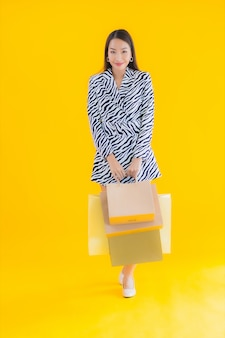 Женщина портрета красивая молодая азиатская с хозяйственной сумкой от розницы и универмага на желтом цвете