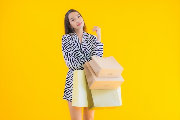 Portrait beautiful young asian woman with shopping bag from retail and department store on yellow