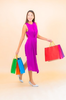 고립 된 색상 배경에 쇼핑백과 세로 아름 다운 젊은 아시아 여자