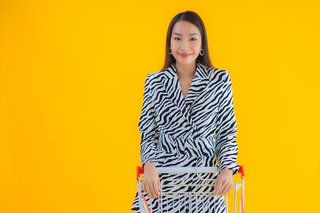 肖像画黄色の食料品の買い物のためのショッピングカートと美しい若いアジア女性