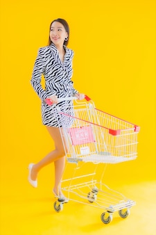 Portrait beautiful young asian woman with shopping cart for grocery shopping on yellow