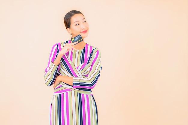色の上のスマートな携帯電話とクレジットカードを持つ肖像画の美しい若いアジアの女性