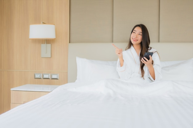 Portrait beautiful young asian woman with smart mobile phone in bedroom
