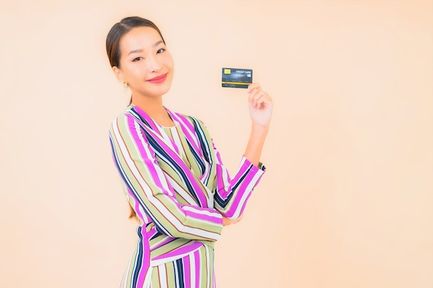 Portrait beautiful young asian woman with smart mobile phone and credit card on color