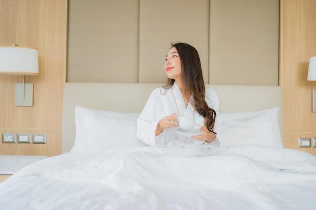 Женщина портрета красивая молодая азиатская с умным мобильным телефоном в спальне
