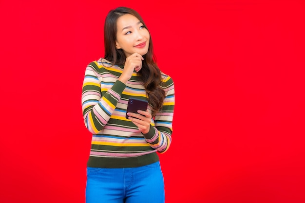 붉은 벽에 스마트 휴대 전화와 세로 아름 다운 젊은 아시아 여자