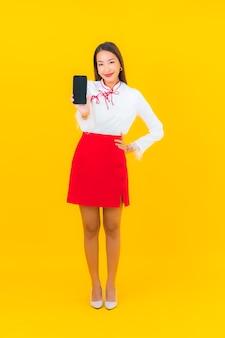 Женщина портрета красивая молодая азиатская с умным мобильным телефоном на желтом