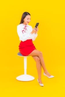 黄色のスマート携帯電話を持つ美しい若いアジア女性の肖像画
