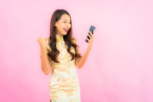 Bella giovane donna asiatica del ritratto con il telefono cellulare astuto sulla parete di colore rosa