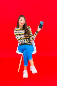 Bella giovane donna asiatica del ritratto con il telefono cellulare astuto sulla parete isolata rossa
