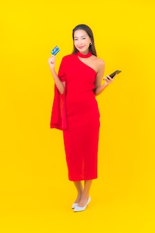 신용 카드와 스마트 휴대 전화와 초상화 아름 다운 젊은 아시아 여자