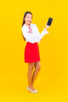 Portrait beautiful young asian woman with smart mobile phone on yellow