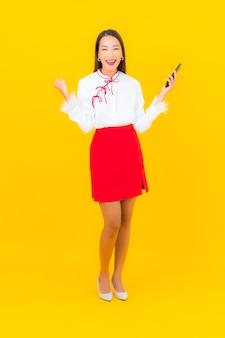 Bella giovane donna asiatica del ritratto con il telefono cellulare astuto su yellow