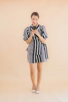スマート携帯電話を持つ美しい若いアジア女性の肖像画