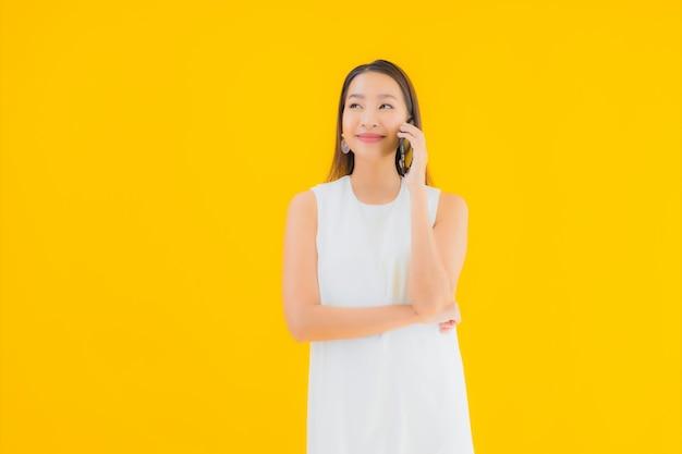 세로 스마트 휴대 전화와 함께 아름 다운 젊은 아시아 여자