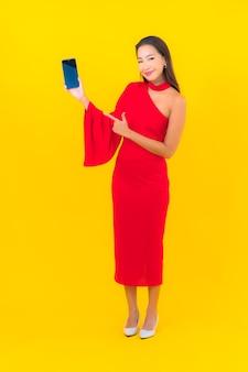 スマート携帯電話と肖像画の美しい若いアジアの女性