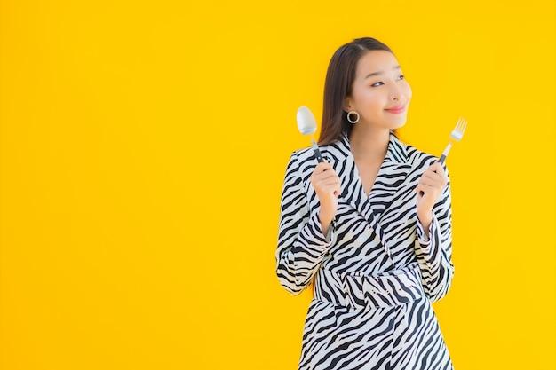 La bella giovane donna asiatica del ritratto con il cucchiaio e la forchetta pronti per mangia su giallo