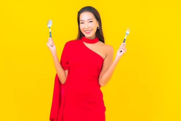 Ritratto bella giovane donna asiatica con cucchiaio e forchetta pronti da mangiare