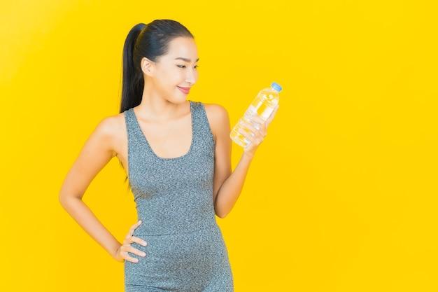 노란색 벽에 운동복과 병 물 초상화 아름 다운 젊은 아시아 여자