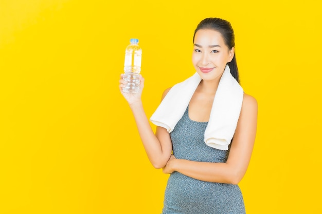 Portrait beautiful young asian woman with sportswear and bottle water on yellow wall