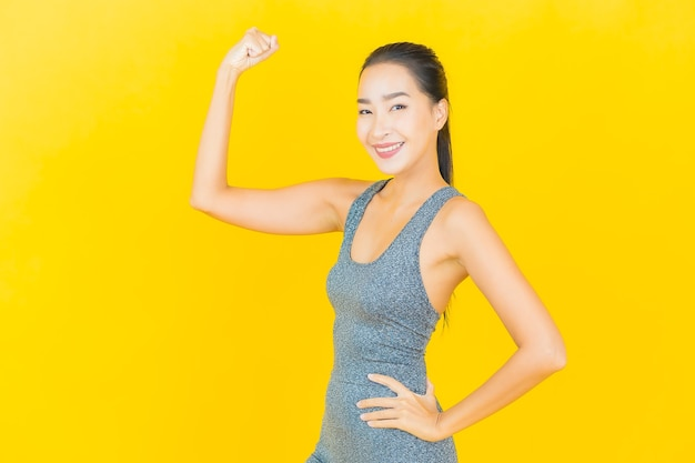 Portrait beautiful young asian woman with sportswear ready for exercise on yellow wall