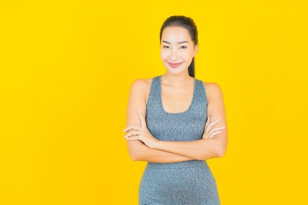노란색 벽에 운동을위한 준비 운동복 초상화 아름 다운 젊은 아시아 여자
