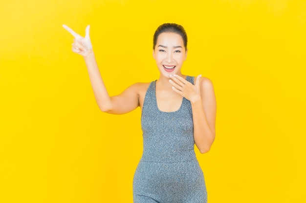 黄色の壁に運動の準備ができてスポーツウェアと肖像画の美しい若いアジアの女性