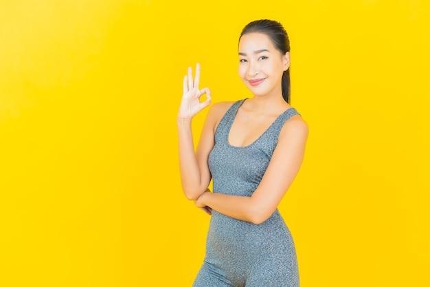 Женщина портрета красивая молодая азиатская с спортивной одеждой готова для тренировки на желтой стене