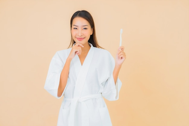 Portrait beautiful young asian woman with toothbrush on beige