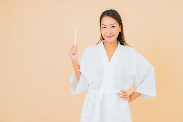 ベージュの歯ブラシと肖像画の美しい若いアジアの女性